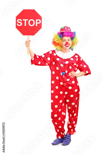 Full length portrait of a clown holding a stop sign