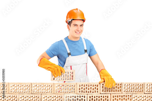 Male construction worker holding a brick behind brick wall
