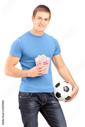 Male sports fan holding a football and popcorn box