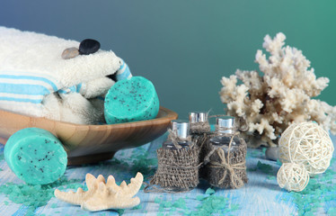 Oil spa, towels candles on wooden table on blue background