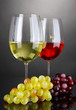 Red and white wine in glasses on grey background