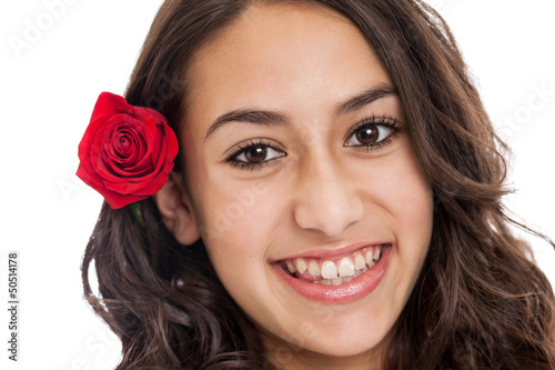 Cute tween girl with red rose in her hair portrait