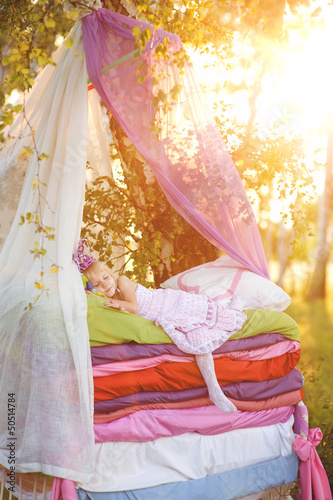 "girl sleeps on a bed. the fairy tale ""the princess on a pea"""