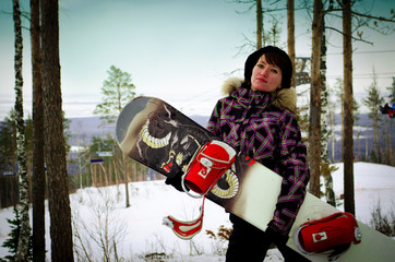 Young woman with snowboard on a mountain top