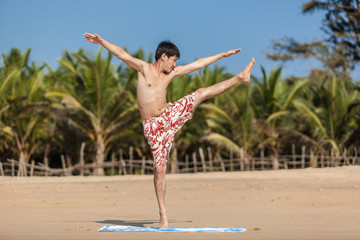 Guy of Asian appearance practices yoga on a beach