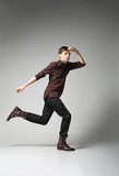 Young fashion male jumping on grey background