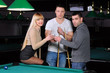 Young attractive people aim at game at billiards
