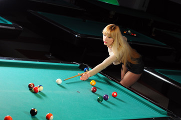 beautiful blonde is playing at billiards