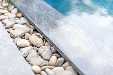Pool with pebble border framed with stone.