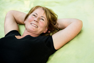 Smiling mature woman lying outdoor