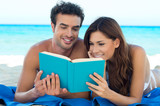 Couple Reading Book At The Beach