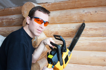Worker with  chainsaw  in wooden house
