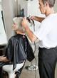 Hairdresser Straightening Female Client's Hair