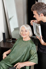 Woman With Hair Stylist Holding Mirror