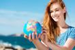 canvas print picture - junge frau mit globus am meer