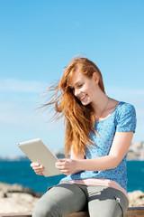 frau liest ein ebook am meer