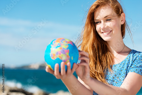 Leinwanddruck Bild junge frau mit globus am meer