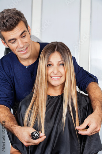 Woman With Hairdresser Measuring Her Hair At Salon