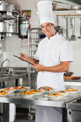 Male Chef With Clipboard At Kitchen