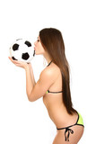 Girl in a swimsuit holding and kissing a soccer ball on a white