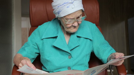 old woman sitting on chair and reading newspaper