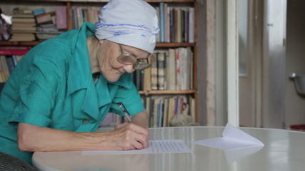 old woman in glasses writing letter