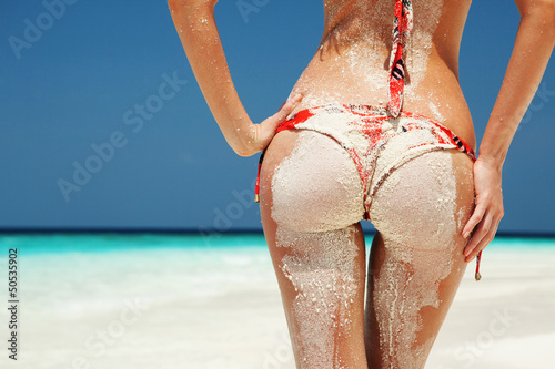 Leinwanddruck Bild Sexy sandy woman buttocks on the beach background
