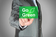 Businessman pushes touch screen go green button. Eco concept..