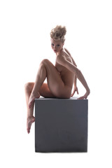 Attractive naked girl posing sitting on cube