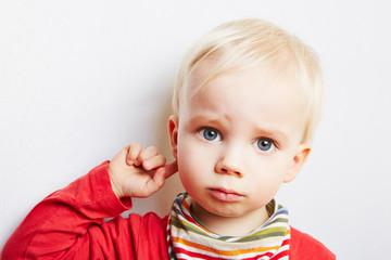 Kind mit Finger am schmerzenden Ohr
