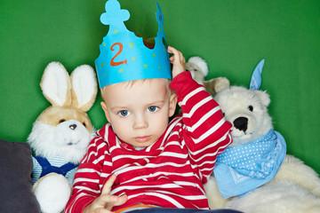 Trauriges Kind mit Krone und Kuscheltieren