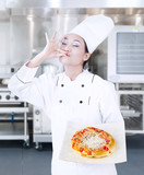 Delicious pizza hold by chef on kitchen