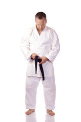 Karateka fastening his belt