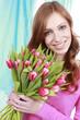 Glückliche Frau mit rosa Tulpenstrauss