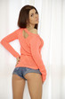 Young slim sexy woman in orange sweater against the window
