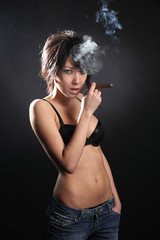 Hot sexy woman with bra smoking cigar. Shrouded in smoke