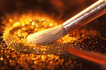 Close-up on makeup brush and gold shining powder.