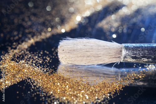 Close-up on makeup brush and gold shining powder.