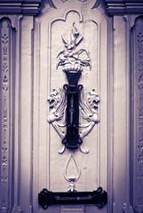Figuras misticas talladas en puerta con aldaba