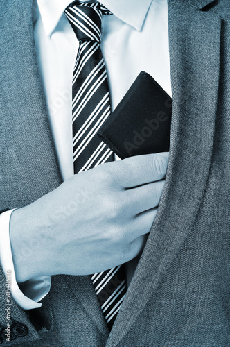 a man in a suit taking out his wallet