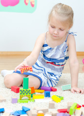 Cute little girl playing with building blocks