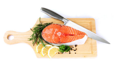 Fresh salmon steak on cutting board, isolated on white