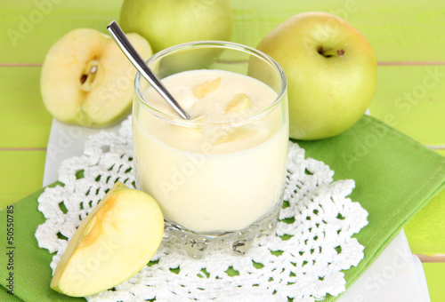 Delicious yogurt in glass with apple on blue tablecloth