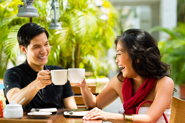 Asian man and woman in restaurant or cafe