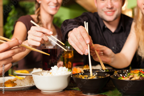 Young people eating in Thai restaurant - 50554356