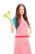 Young woman wearing red apron and holding plastic spoons