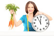 Young woman with measuring tape holding carrots and a wall clock