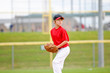 Youth baseball pitcher in red jersey