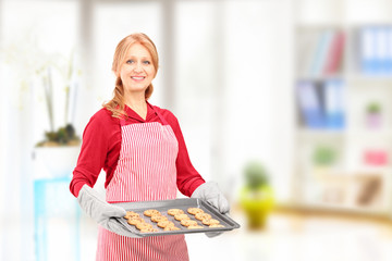 Mature woman holding a tray with baked cookies and posing at hom