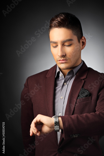 Handsome man checking the time on his wrist watch